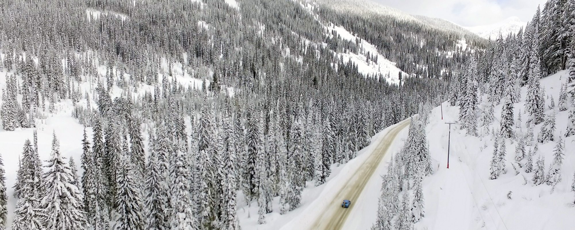 EV driving up a snow packed road